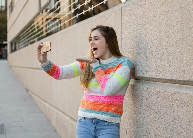 Happy pretty teenager girl using smart mobile phone excited blowing a kiss and waving to followers friends or family recording video or chatting. Video call In technology Communications and Blogging.