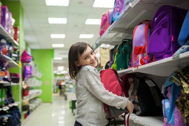 Portrait of   girl of 8 years in shop choosing  briefcase  for school