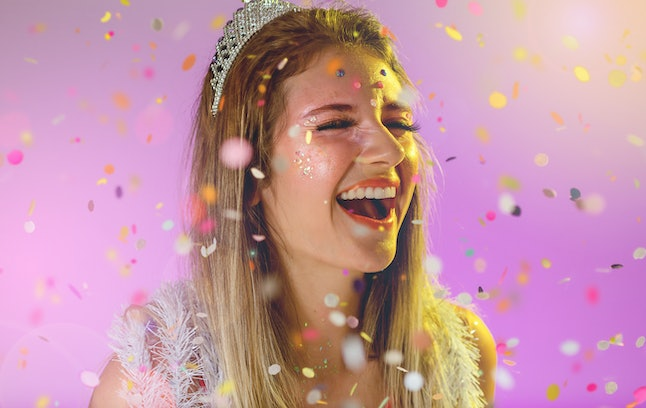 Carnaval Brazil. Excited and Cheerful. Throwing confetti. Face of young woman with colorful makeup, dressed up for fun. Bright background. Party concept, celebration and festival.