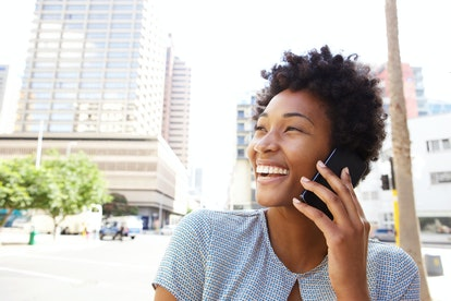 Closeup portrait of a cheerful young woman making a phone call outdoors in the city