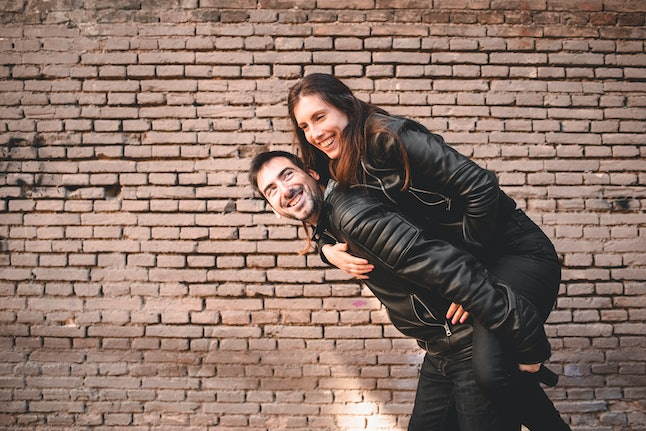Couple in piggyback having a good time of laughter and love to celebrate their upcoming wedding.