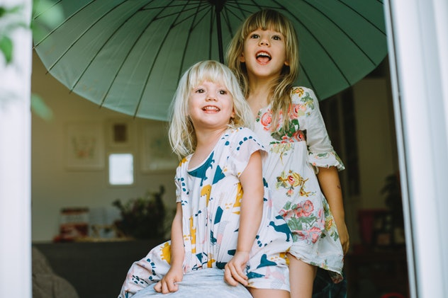 Two little cute sisters laughing together and holding a big green umbrella