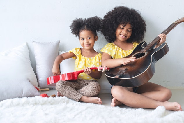 Two African sisters and sisters are sitting and playing guitar on the floor.