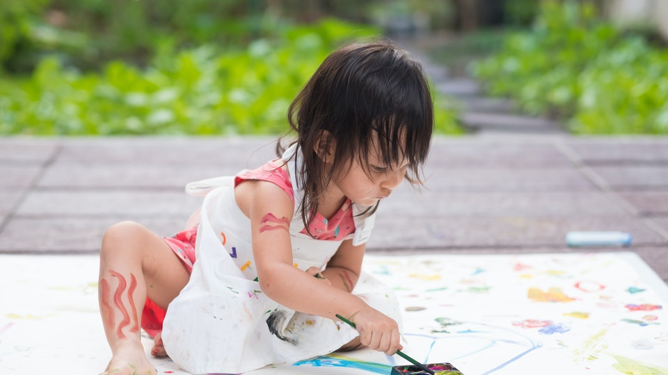 Adorable asian little girl is playing by painting water color outside the house, concept of art education for kid.