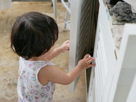 Selective focus of little curious Asian baby girl's hands open a cabinet of daddy's mechanic tools - baby's curiosity since their early age