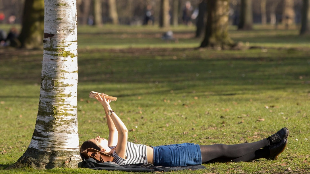 A woman enjoys reading her book in the sunshine in Hyde Park on what is set to be the warmest day in February since records began.