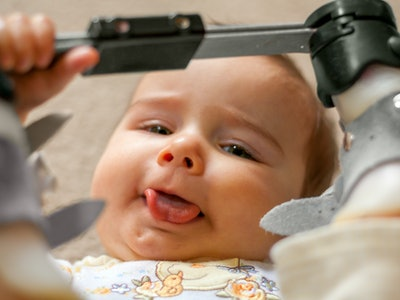 A nine month old baby with a tongue tie and orthopedic shoes lays on her back with her tongue sticking out as much as possible as she holds the bar between her orthopedic shoes for a club foot.