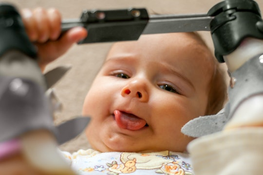 A nine month old baby with a tongue tie and orthopedic shoes lays on her back with her tongue sticki...