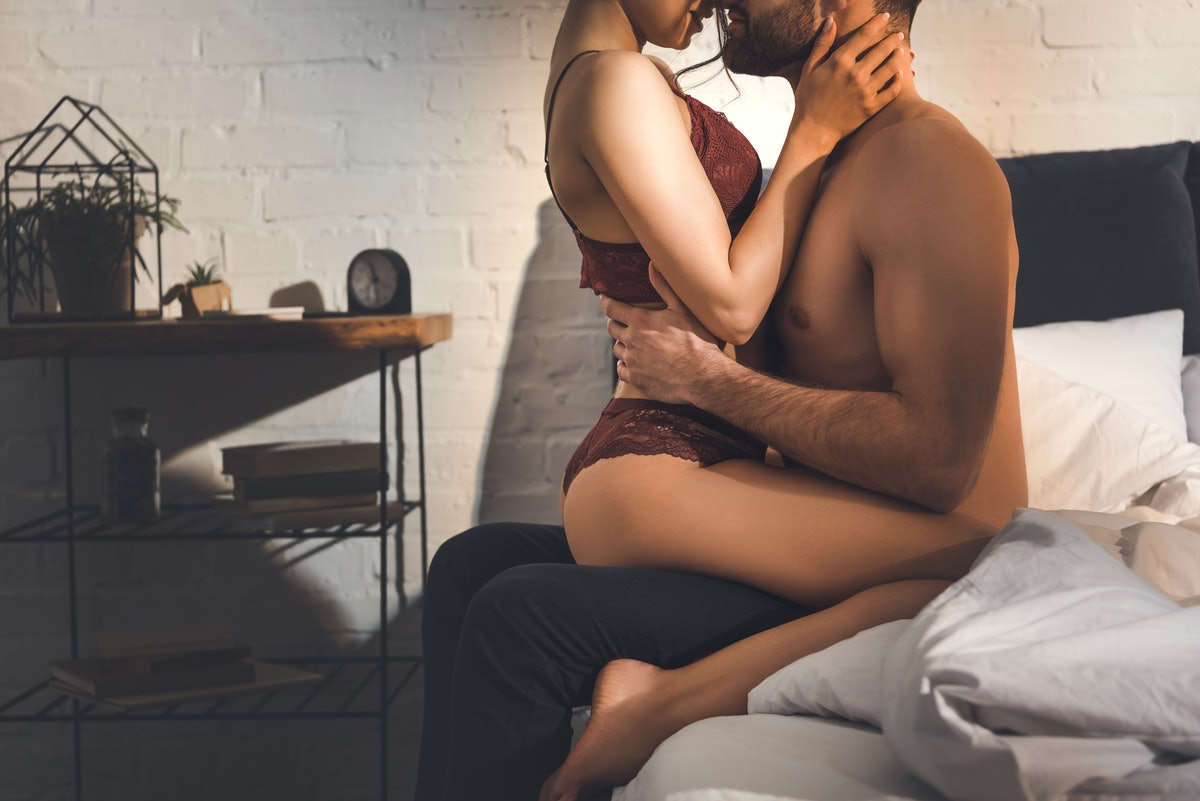 cropped view of sexy couple passionately embracing on bed at home