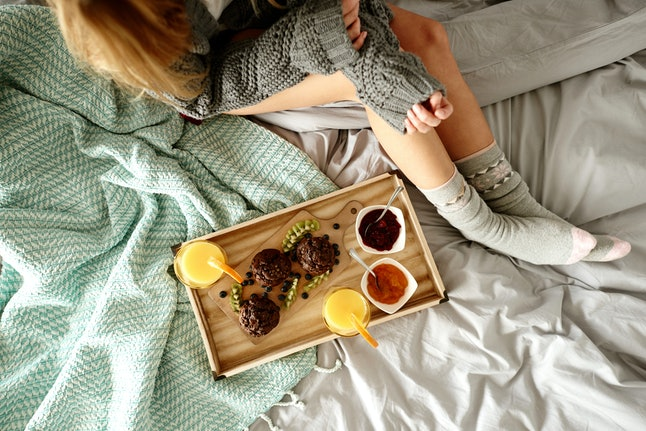 Unrecognizable woman and breakfast on bed