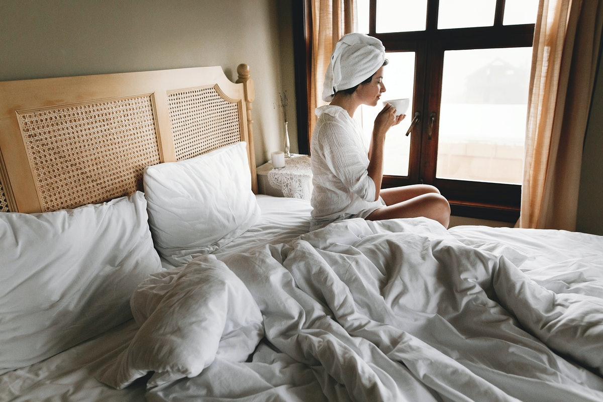 Beautiful happy young woman drinking coffee or tea in bed in hotel room or home bedroom. Stylish  brunette girl with white towel enjoying morning in soft light, looking at window. Space for text