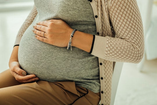 Pregnant belly. A woman touching her third-trimester pregnant belly