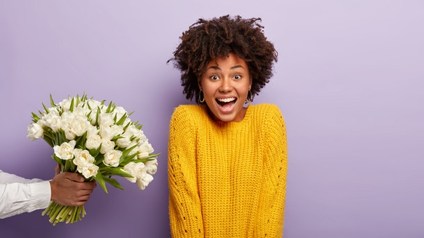 Date and flowers concept. Small present to beloved girlfriend. Man makes pleasant surprise for female, stretches hand with spring white tulips, wears bright yellow jumper isolated on purple background