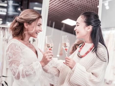 Pleasant communication. Joyful nice women talking about future wedding while drinking champagne