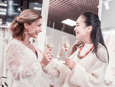 Pleasant communication. Joyful nice women talking about future wedding while drinking champagne
