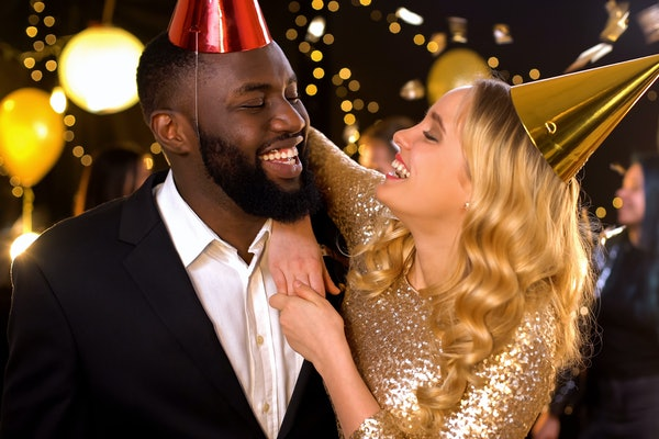 Glad mixed-race couple in party hats celebrating birthday, holiday entertainment