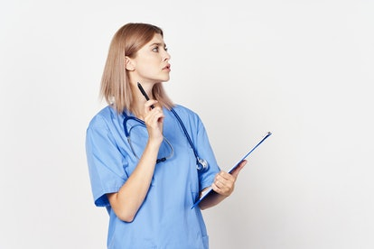 woman doctor in medical coat with a stethoscope around her neck holding documents in her hand