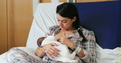 Mom breastfeeding newborn baby infant at hospital, first day of life