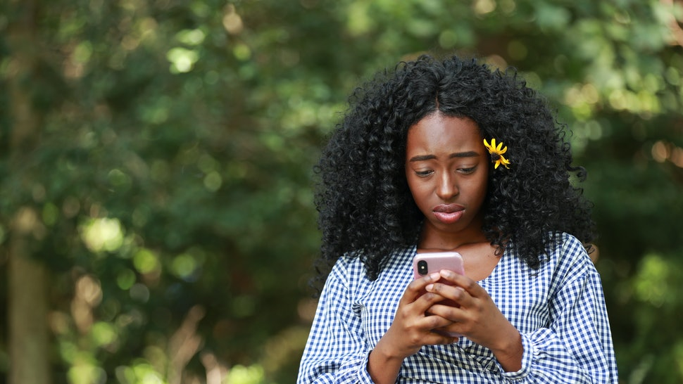 Young disappointed African American woman texting in sunny park