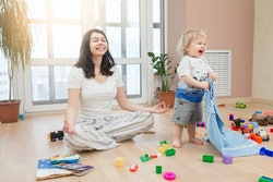 Portrait of young happy yoga mom spending time with her little baby boy, meditating in lotus positio...