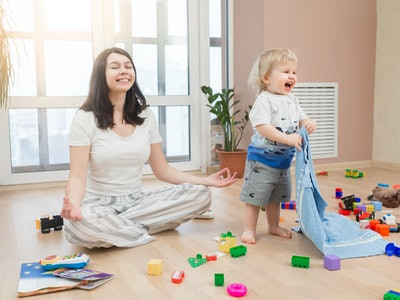 Portrait of young happy yoga mom spending time with her little baby boy, meditating in lotus position while her kid son playing games at home