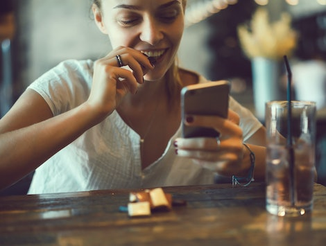 young pretty brunette woman eat chocolate in cafe, using smartphone, touch screen display, sweet food, tasty breakfast, close up portrait, hipster girl, fanny