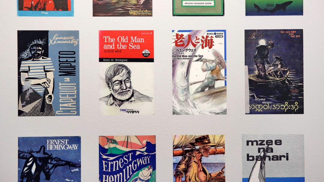 """A selection of Ernest Hemingway's """"The Old Man and the Sea"""" book covers are displayed in many languages at the """"Ernest Hemingway: A Life Inspired"""" exhibition, featuring books and belongings from the archives of author Hemingway, at the John F. Kennedy Presidential Library and Museum in Boston, . The Boston complex has become the world's leading research center for Hemingway studies"""