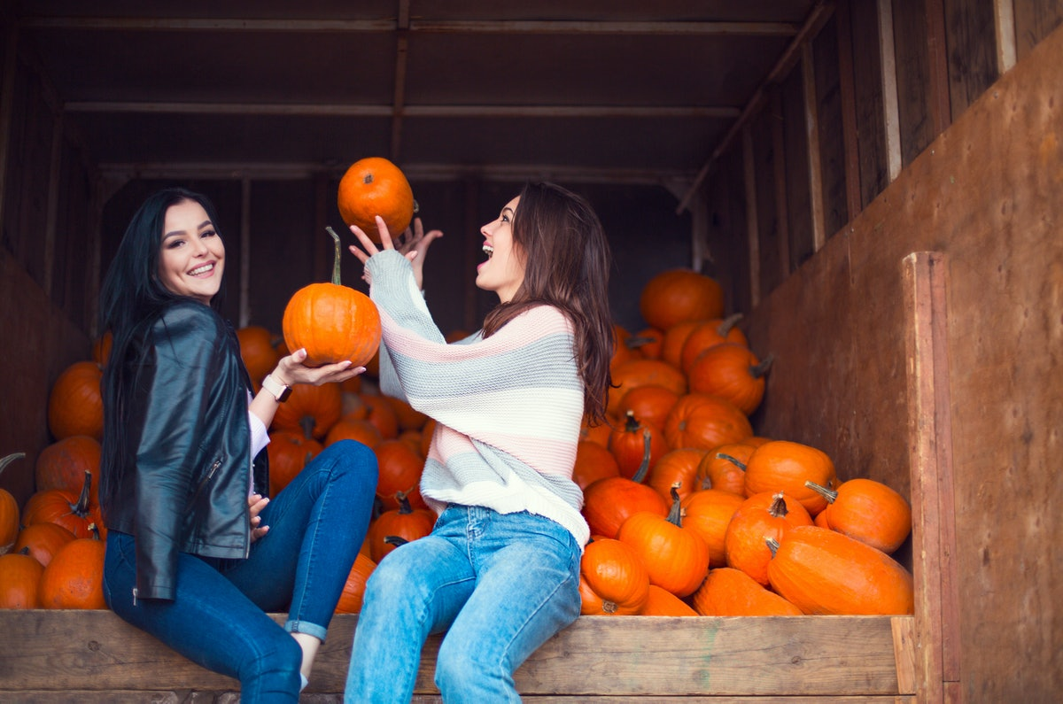 Two women laughing candidly surrounded by pumpkins is the perfect picture pose to pair with pumpkin ...