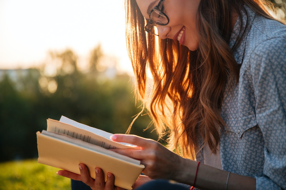 Cropped image of smiling brunette woman in eyeglasses reading book in park