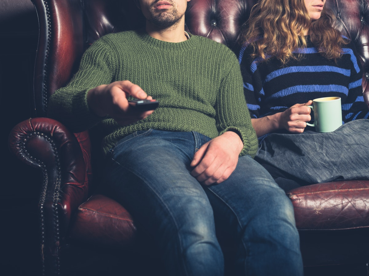 A bored young couple are sitting on a sofa at home watching television