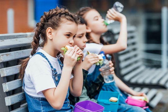 Three child eat, appetizing school lunch. Healthy school lunch: apple, juice, hamburger, vegetable,after education..