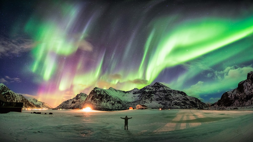 Aurora borealis (Northern lights) over mountain with one person at Skagsanden beach, Lofoten islands, Norway