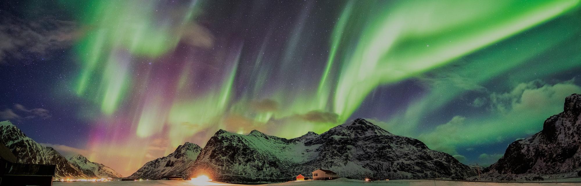 Aurora borealis (Northern lights) over mountain with one person at Skagsanden beach, Lofoten islands...