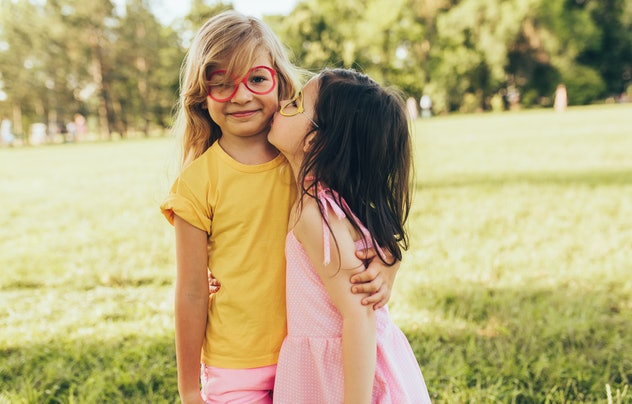Two positive children shares love and frienship. Two little girls enjoying summertime in the park. Two sisters having fun on sunlight outdoors. Childhood and friendship concept
