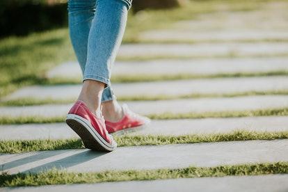 Walking women jeans and sneaker shoes