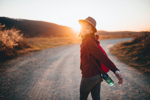 Happy girl wearing backpack and hat hiking alone during sunset