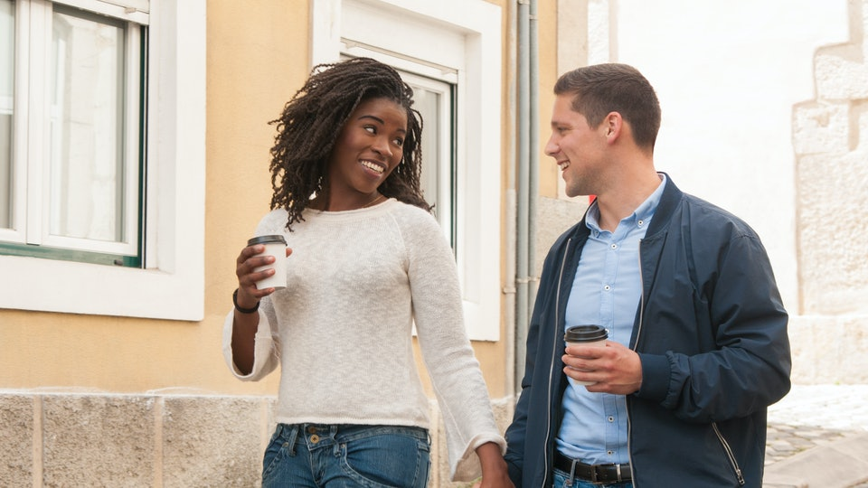 Happy cheerful interracial couple enjoying date. Afro American girl and her Caucasian boyfriend holding hands, walking around old city and enjoying coffee break. Love and leisure concept