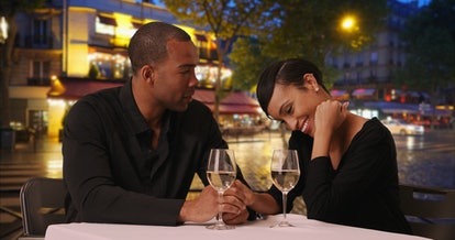African woman and boyfriend eating at fine-dine restaurant on romantic night out