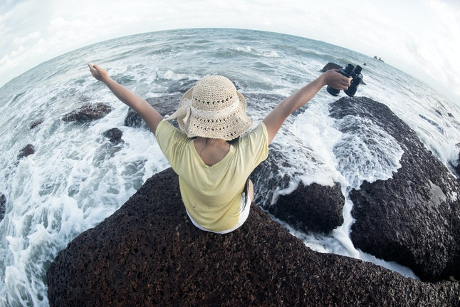 Asian pretty female sitting and resting on rocks with strong waves and holding a  Binoculars happiness and fun.
