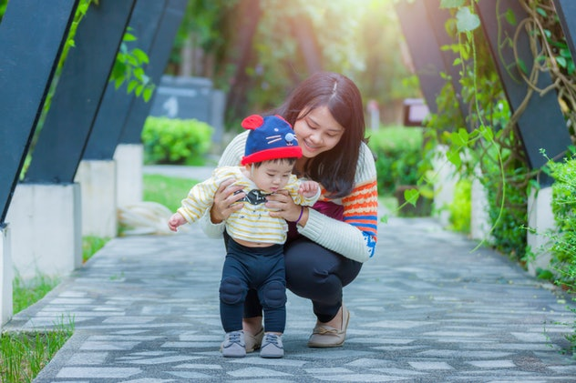 Mother and little asian baby boy in  the nature park. Concept of friendly family and of summer vacation.