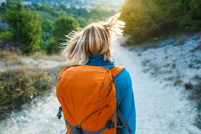 A girl with a backpack walks along the mountain path. A woman is walking through the forest at sunset. A blonde is traveling with a backpack. Hair beautifully fluttering in the wind.