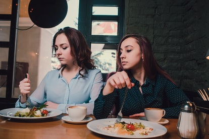 Two unhappy lesbians not talking to each other after having quarrel during lunch at coffee shop: sad redhead woman feeling lonely while her girlfriend sitting next to her.