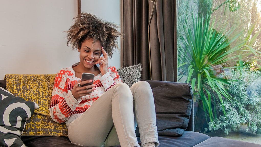 Texting lovely message to him. Attractive young woman holding smart phone and smiling . Portrait of an attractive young woman reading text messages on a cellphone while relaxing on a sofa at home