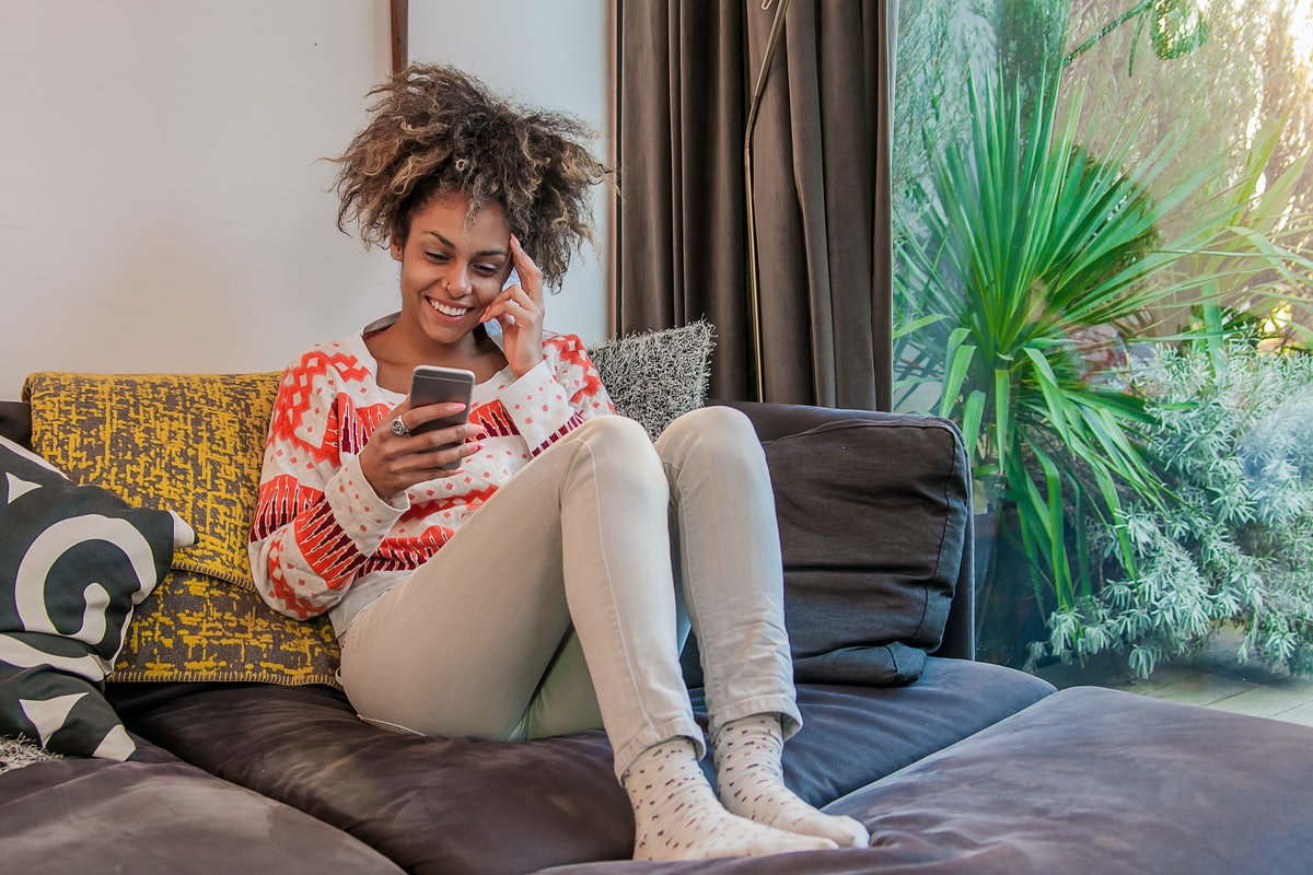Texting lovely message to him. Attractive young woman holding smart phone and smiling . Portrait of ...