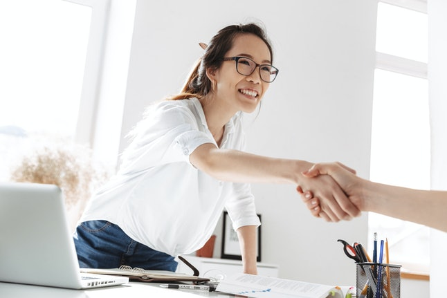 Smiling asian business woman in eyeglasses on meeting doing handshake in office
