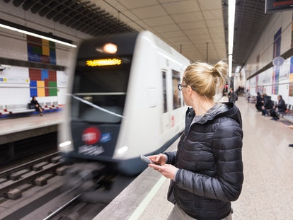 Young casual woman with a cell phone in her hand waiting on the platform of a metro station for metr...