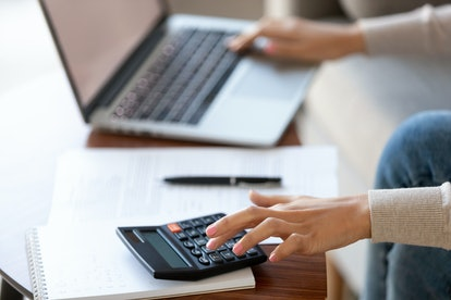 Businesswoman using calculator and laptop for budget cost money management strategy, female hands calculating bills finances expenses taxes doing paperwork at work desk, bookkeeping concept, close up