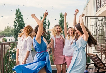 A group of women party and dance in the sunshine on a balcony celebrating a bachelorette party.