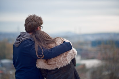 Couple hugging and looking at the horizon at the autumn. Back turned