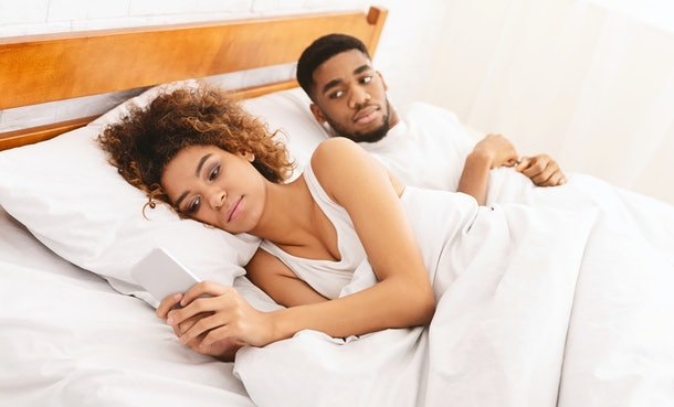 Distrust, jealousy and relationship problems. Young woman turned her back to man, reading message on phone from her lover, suspicious boyfriend trying to peek at screen, panorama